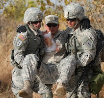 Two medical field Soldiers transport a simulated casualty using a two-man-carry technique Oct. 28 during EFMB testing. Candidates from various units of the 1st Inf. Div. were on hand competing for the highly regarded badge. This was one of many tasks the medics had to correctly complete during the EFMB testing.