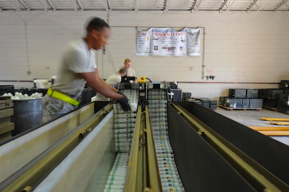 The munitions maintenance crew feeds 25mm rounds through a machine at Hurlburt Field, Fla., Nov. 6, 2013. The crew stored all unfired rounds for later use. (U.S. Air Force Photo/Staff Sgt. John Bainter)