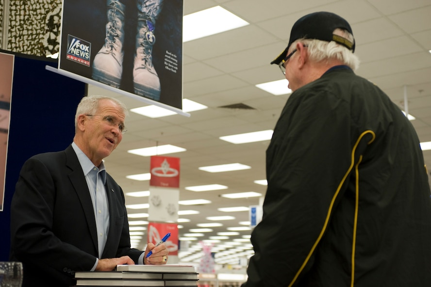 "Oliver North, signs an autograph for retired Chief Master Sgt. Grady Griffin, at the Exchange during a book signing Nov. 9, 2013, at Nellis Air Force Base, Nev. North signed autographs for his book ""American Heroes, On the Homefront"" during his visit to Nellis AFB. North served 22 years in the U.S. Marine Corps and retired at the rank of lieutenant colonel. (U.S. Air Force photo by Airman 1st Class Christopher Tam)"