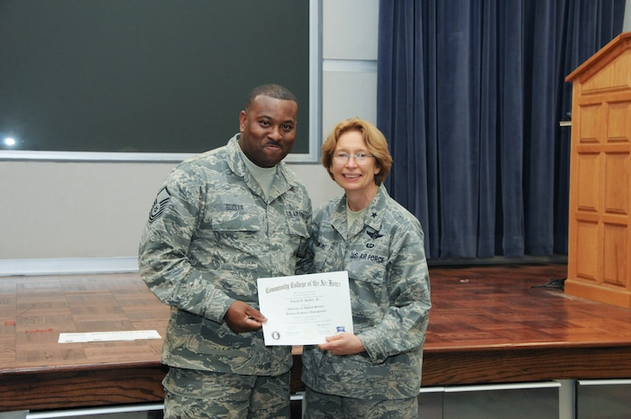 U.S. Air Force Master Sgt. Ronald Sudler, left, a member of the 166th Force Support Squadron, 166th Airlift Wing, receives a certificate from Brig. Gen. Carol Timmons, assistant adjutant general for air, Delaware National Guard to recognize Sudler's attainment of a Community College of the Air Force associate of applied science degree in human resource management at a CCAF Class of October 2013 graduation ceremony held Nov. 3, 2013 at the New Castle Air National Guard Base, Del. (U.S. Air National Guard photo by Tech. Sgt. Robin Meredith)