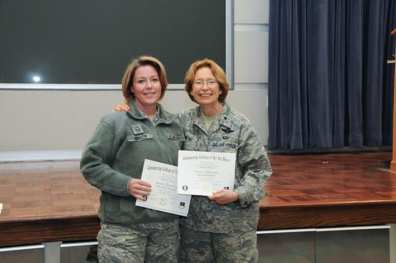 U.S. Air Force Master Sgt. Regina Minzer, left, a member of the 166th Medical Group, 166th Airlift Wing, receives a certificate from Brig. Gen. Carol Timmons, assistant adjutant general for air, Delaware National Guard to recognize Minzer's attainment of a Community College of the Air Force associate of applied science degree in public health technology and a second AAS in allied health sciences at a CCAF Class of October 2013 graduation ceremony held Nov. 3, 2013 at the New Castle Air National Guard Base, Del. (U.S. Air National Guard photo by Tech. Sgt. Robin Meredith)