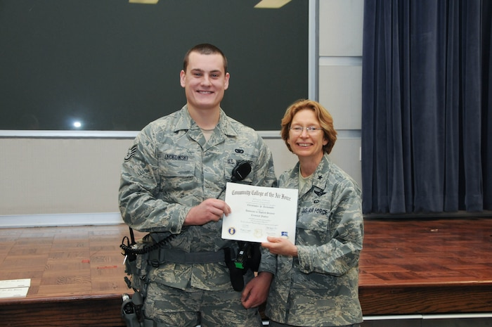 U.S. Air Force Staff Sgt. Christopher Jackowski, left, a member of the 166th Security Forces Squadron, 166th Airlift Wing, receives a certificate from Brig. Gen. Carol Timmons, assistant adjutant general for air, Delaware National Guard to recognize Jackowski's attainment of a Community College of the Air Force associate of applied science degree in criminal justice at a CCAF Class of October 2013 graduation ceremony held Nov. 3, 2013 at the New Castle Air National Guard Base, Del. (U.S. Air National Guard photo by Tech. Sgt. Robin Meredith)