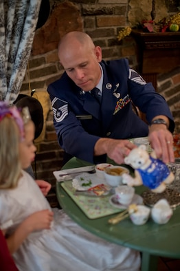 "Senior Master Sgt. Greg Wolhfeil pours tea for his daughter at the Avalon Tearoom & Pastry Shoppe in White Bear Lake, Minn. on Nov. 8.  After returning from a long training course away from home, Wolhfeil planned special 'dates' with each one of his family members to solidify family bonds.  ""When I asked my 7-year old daughter where she wanted to go, it was her idea to go to tea,"" said Wolhfeil.  (U.S. Air National Guard photo by Tech. Sgt. Lynette Olivares/Released)"