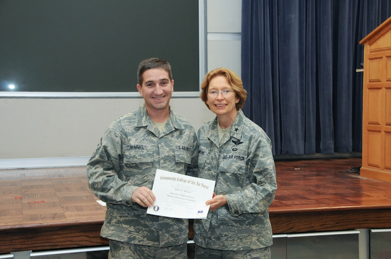 U.S. Air Force Master Sgt. Shane Hummel, left, a member of the 166th Civil Engineer Squadron, 166th Airlift Wing, receives a certificate from Brig. Gen. Carol Timmons, assistant adjutant general for air, Delaware National Guard to recognize Hummel's attainment of a Community College of the Air Force associate of applied science degree in aircraft maintenance technology at a CCAF Class of October 2013 graduation ceremony held Nov. 3, 2013 at the New Castle Air National Guard Base, Del. (U.S. Air National Guard photo by Tech. Sgt. Robin Meredith)