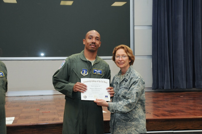 U.S. Air Force Tech. Sgt. Alvin Henson, left, a member of the 142nd Airlift Squadron, 166th Airlift Wing, receives a certificate from Brig. Gen. Carol Timmons, assistant adjutant general for air, Delaware National Guard to recognize Henson's attainment of a Community College of the Air Force associate of applied science degree in aviation operations at a CCAF Class of October 2013 graduation ceremony held Nov. 3, 2013 at the New Castle Air National Guard Base, Del. (U.S. Air National Guard photo by Tech. Sgt. Robin Meredith)