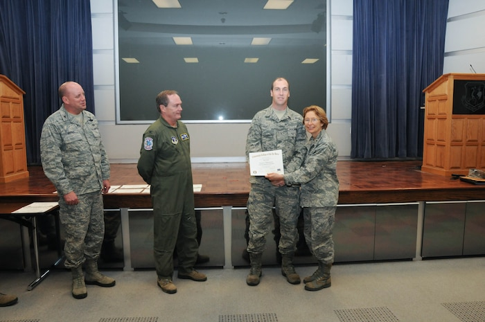 U.S. Air Force Tech. Sgt. Jon Goe, second from right, a member of the 166th Network Warfare Squadron, 166th Airlift Wing, receives a certificate from Brig. Gen. Carol Timmons, assistant adjutant general for air, Delaware National Guard to recognize Goe's attainment of a Community College of the Air Force associate of applied science degree in electronic systems technology at a CCAF Class of October 2013 graduation ceremony held Nov. 3, 2013 at the New Castle Air National Guard Base, Del. 166th AW Commander Col. Mike Feeley, second from left, is next to 166th AW Vice-Commander Col. Dave Byerly. (U.S. Air National Guard photo by Tech. Sgt. Robin Meredith)