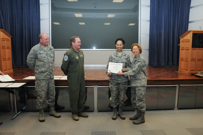 U.S. Air Force Tech. Sgt. Zaquette Everett, second from right, a member of the 166th Airlift Wing, receives a certificate from Brig. Gen. Carol Timmons, assistant adjutant general for air, Delaware National Guard to recognize Everett's attainment of a Community College of the Air Force associate of applied science degree in vehicle maintenance at a CCAF Class of October 2013 graduation ceremony held Nov. 3, 2013 at the New Castle Air National Guard Base, Del. 166th AW Commander Col. Mike Feeley, second from left, is next to 166th AW Vice-Commander Col. Dave Byerly. (U.S. Air National Guard photo by Tech. Sgt. Robin Meredith)