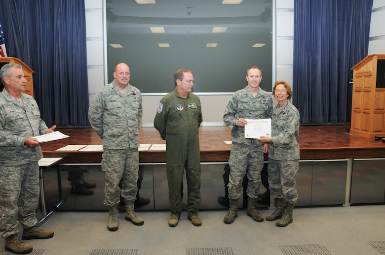 U.S. Air Force Staff Sgt. Wayne Borrmann, second from right, a member of the 166th Civil Engineer Squadron, 166th Airlift Wing, receives a certificate from Brig. Gen. Carol Timmons, assistant adjutant general for air, Delaware National Guard to recognize Borrmann's attainment of a Community College of the Air Force associate of applied science degree in emergency management at a CCAF Class of October 2013 graduation ceremony held Nov. 3, 2013 at the New Castle Air National Guard Base, Del. 166th AW Commander Col. Mike Feeley, center, is next to 166th AW Vice-Commander Col. Dave Byerly, followed by 166th AW Command Chief Master Sgt. Henry Rome (left). (U.S. Air National Guard photo by Tech. Sgt. Robin Meredith)