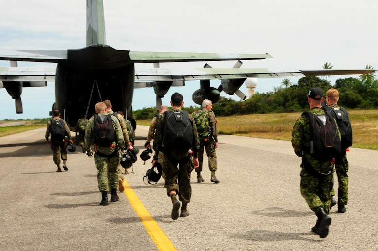 Brazilian, Canadian and U.S. pararescuemen prepare to board a Brazilian C-130E Hercules during CRUZEX at Natal Air Base, Natal, Brazil, Nov. 7, 2013. Exercises such as CRUZEX are designed and led by a host nation, partnering nations receive training opportunities that are beneficial to the entire region. (U.S. Air Force photo by Senior Airman Camilla Elizeu/Released)