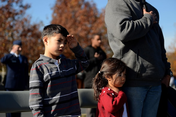 Michael Eloy, 5, (from left) Kimiko Eloy, 3, and their father, Army Maj. Cabera Eloy salute as the colors are presented during a Veterans Day wreath laying ceremony at the Air Force Memorial, Arlington, Va., Nov. 11, 2013. More than 100 veterans, service members, family members and supporters came out for the wreath laying ceremony.