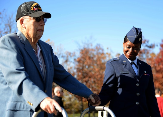 Capt. Natosha Nesby, 779th Medical Operations Squadron, Andrews Air Force Base, Md., escorts an Air Force veteran during a  Veterans Day wreath laying ceremony, Nov. 11, 2013 at the Air Force Memorial in Arlington, Va. More than 100 veterans, service members, family members and supporters came out for the ceremony.