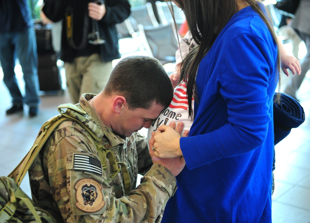 Senior Airman Joseph Tharp, 9th Operations Support Squadron flight equipment technician, hugs his pregnant wife Sarah Nov. 7, 2013, at Sacramento International Airport. Tharp was returning home from a deployment to Afghanistan. (U.S. Air Force photo by Airman 1st Class Bobby Cummings/Released)