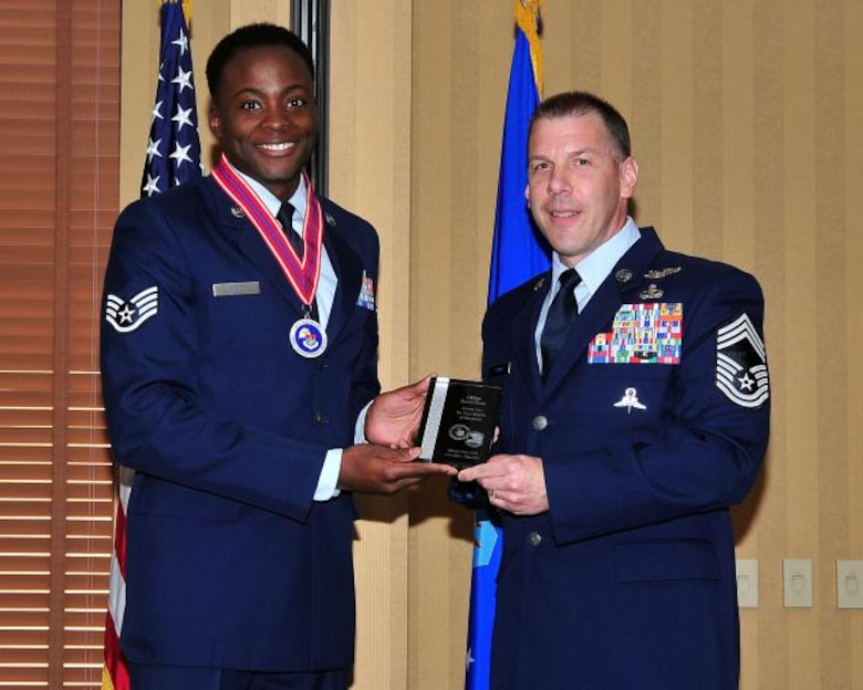 (Left) Staff Sgt. Adam Grant, 12th Air Force (Air Forces Southern) NCOIC of Operations, presents a token of appreciation on behalf of Airman Leadership Class 14A to Chief Master Sgt. David Swan, 563 Rescue Group superintendent, on Davis-Monthan AFB, Ariz., Nov. 7,  2013. (U.S. Air Force Photo by Senior Airman Joshua Slain/Released)