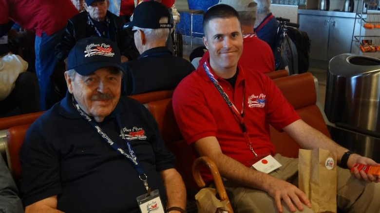 U. S. Air Force Staff Sgt. David Wilcken, 612th Air and Space Operations Center air tasking order production technician, and Robert Yeschek, a World War II, Korean War and Vietnam War veteran, pose at an airport during the Southern Ariz. Honor Flight Trip, Oct. 7, 2013. Wilcken flew with Yeschek during Honor Flight to be his guardian for the duration of the trip. (Courtesy photo)