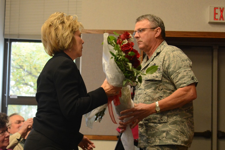 U.S. Air Force Col. Norman Brosi, the outgoing commander of the 139th Mission Support Group, Missouri Air National Guard, hands flowers to his wife during a change of command ceremony at Rosecrans Air National Base, Mo., Oct. 18, 2013. Lt. Col. Gordon Meyer takes the place of Brosi, who retires next week. (U.S. Air National Guard photo by Tech. Sgt. Michael Crane/Released)