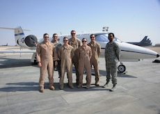 Airmen assigned to the 379th Air Expeditionary Group C-21 Firebass unit pose for a photo at the 379th Air Expeditionary Wing in Southwest Asia, Nov. 5, 2013. The C-21's primary mission here is distinguished visitor transport throughout the U.S. Air Forces Central Command area of responsibility. The members are deployed from Joint Base Andrews, Md., and Scott Air Force Base, Ill. (U.S. Air Force photo/Senior Airman Bahja J. Jones)
