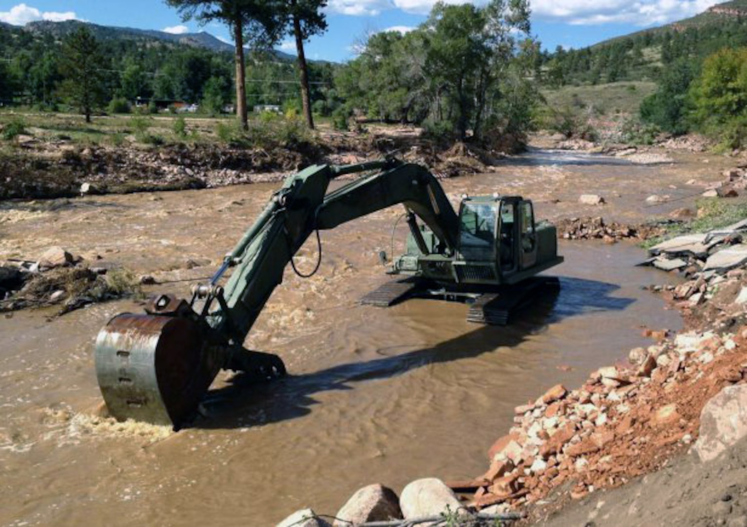 The Texas Army National Guard's 36th Infantry Division's Domestic All-Hazards Response Team-West continues to coordinate assistance requests and support for the Colorado flood relief effort. Pictured here, a military hydraulic excavator works to clear the remainder of a Colorado road after a flood washed it away.