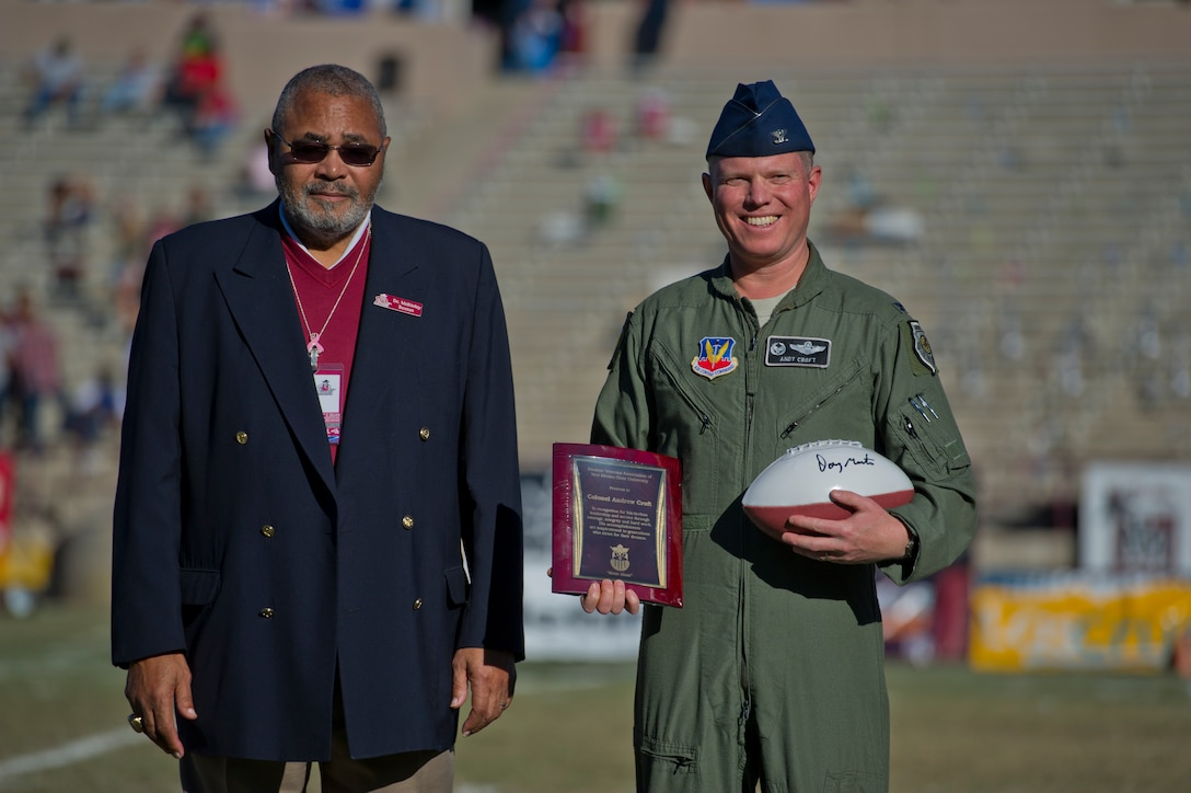 Dr. McKinley Boston, New Mexico State University athletic director, presents a recognition plaque and football to Col. Andrew Croft, 49th Wing commander, at Aggie Memorial Stadium in Las Cruces, N.M., Nov. 9. NMSU hosted Boston College for their annual military appreciation game, which honored current and past military veterans. (U.S. Air Force photo by Airman 1st Class Aaron Montoya/Released)