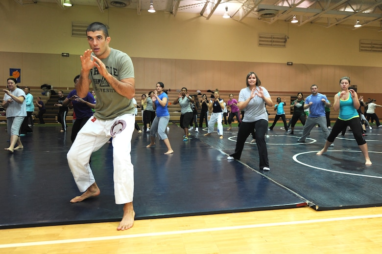 Rener Gracie, Gracie Academy Women Empowered self-defense seminar instructor, demonstrates a combat base pose as Team Malmstrom members follow. The weeklong self-defense seminar trained nearly 100 participants to become certified instructors. (U.S. Air Force photo/Senior Airman Katrina Heikkinen)