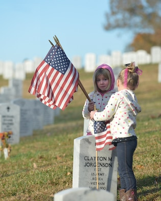 KNOXVILLE, Tenn. - Brooke and Ryleigh, the 4-year-old twin daughters, of Tech. Sgt. Donald Noel, an instructor at the I.G. Brown Training and Education Center, place flags at the Tennessee Veterans' Cemetery, Nov. 9, 2013. (U.S. Air National Guard photo by Master Sgt. Kurt Skoglund/Released)