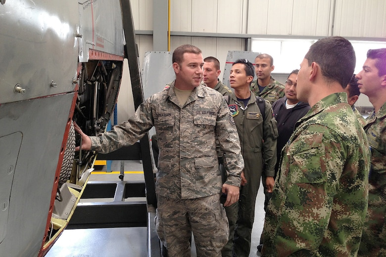 Tech. Sgt Jason Sanderson, a crew chief in the Kentucky Air National Guard's 123rd Global Mobility Squadron, explains C-130 engine components and inspection procedures to members of the Columbia Air Force during a training event held in Bogota, Columbia, in August and September 2013. (U.S. Air National Guard Photo)