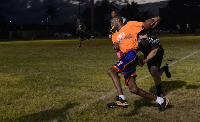 Derek Thorton, Helicopter Sea Combat Squadron 25, runs down the field and avoids having his flag taken Nov. 13, 2013, on Andersen Air Force Base, Guam. The HSC-25 intramural flag football team defeated the 36th Civil Engineer Squadron 40-0. (U.S. Air Force photo by Airman 1st Class Emily A. Bradley/Released)