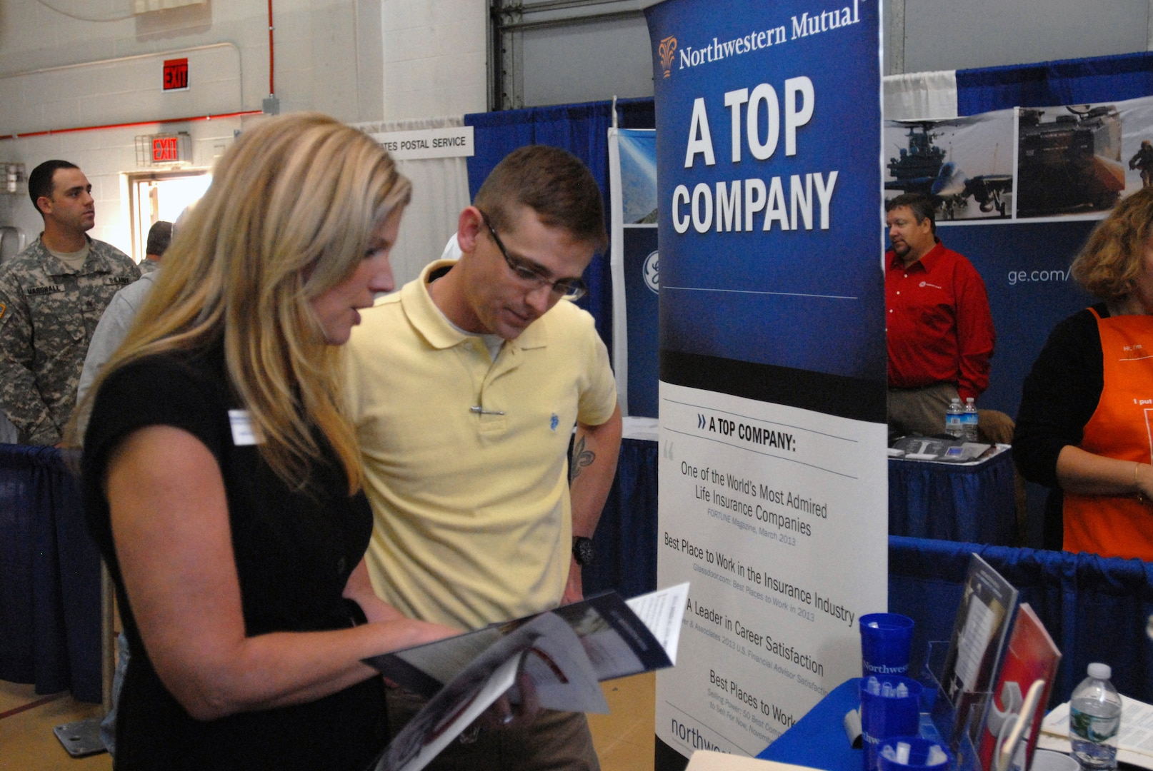 """Kristen Cargill, a representative from Northwestern Mutual Financial Network, speaks with New York Army Guard Soldier 1st Lt. John Scott at the U.S. Chamber of Commerce's """"Hiring Our Heroes"""" job fair held at the New York National Guard armory Oct. 16."""
