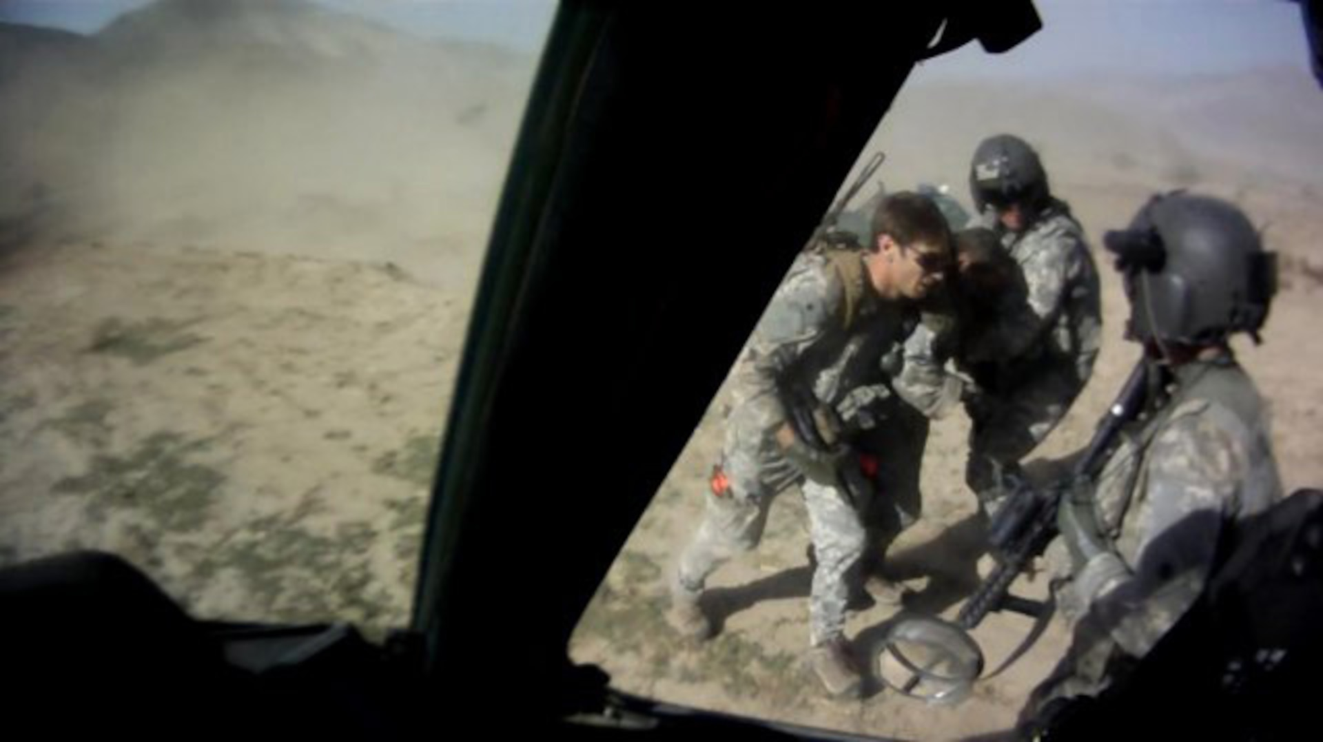 Capt. William Swenson, left, assists severely wounded Sgt. 1st Class Kenneth Westbrook onto a UH-60 Black Hawk helicopter, Sept. 8, 2009, during the Battle of Ganjgal, in Afghanistan. Sgt. Marc Dragony, right, and Staff Sgt. Kevin Duerst, foreground holding an M4 carbine, from the California National Guard, assist.
