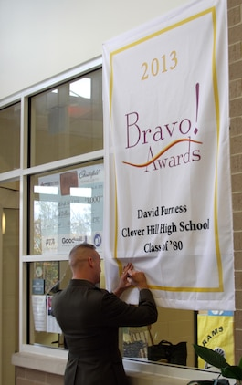 U.S. Marine Corps Brigadier General David Furness, Legislative Assistant to the Commandant of the Marine Corps, signs a banner commemorating his Bravo Award at Clover Hill High School, Nov. 8, 2013. Furness returned to his hometown to accept a Bravo Award from the Chesterfield Public Education Foundation, which recognizes outstanding achievement by graduates from Chesterfield County Public Schools, but also took the opportunity to volunteer to speak at local high schools. (U.S. Marine Corps photo by Cpl. Aaron Diamant/Released)