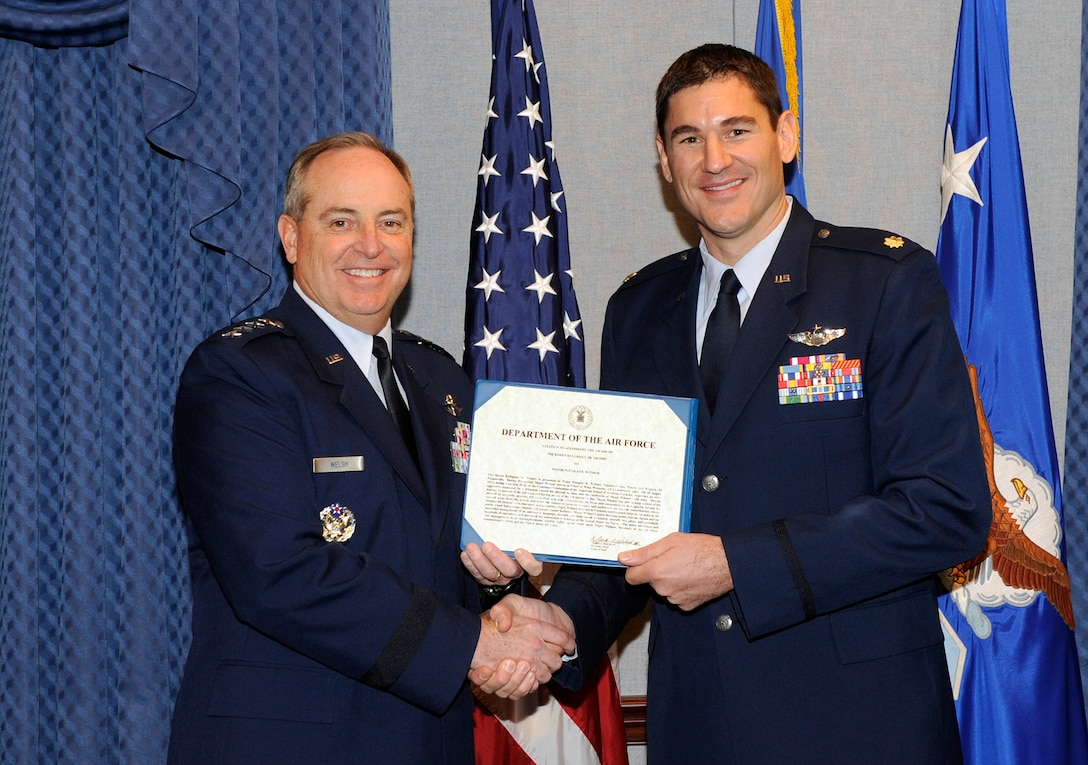 Maj. Douglas Witmer is honored by Air Force Chief of Staff Gen. Mark A. Welsh III during a ceremony  Nov. 14, 2013, in the Pentagon. Witmer is this year's recipient of the Koren Kolligian Jr. trophy for outstanding Airmanship. Several members of the Kolligian family were present during the ceremony. (U.S. Air Force photo/Andy Morataya)