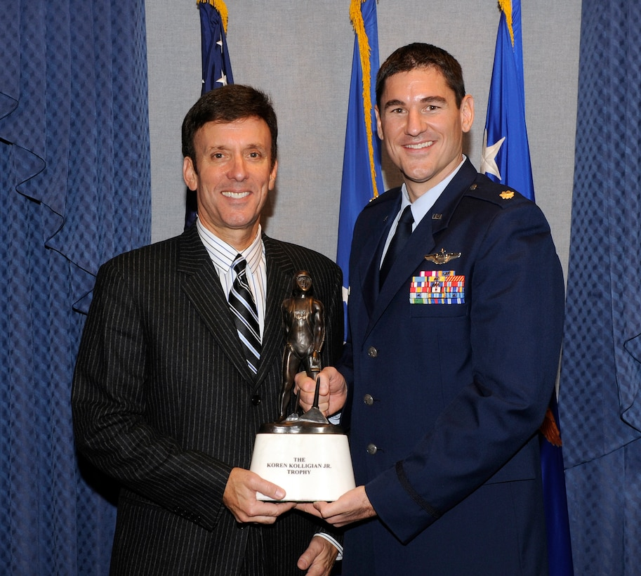 Cory Kolligian, representing the Kolligian family, congratulates Maj. Douglas Witmer, this year's recipient of the Kolligian trophy, during an award ceremony honoring Witmer  Nov. 14, 2013, in the Pentagon. Witmer is this year's recipient of the Koren Kolligian Jr. trophy for outstanding Airmanship.