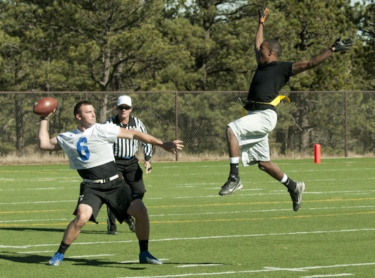 Airman 1st Class Devin Harris jumps to impede the vision of former U.S. Air Force Academy quarterback, 2nd Lt. Brian Lindsay during a game at the Academy Nov. 9, 2013. The game determined which base would have their name etched into the Rocky Mountain Regional Military Championship plaque. Harris is assigned to the 90th Maintenance Operations Squadron. Lindsay is the USAFA Prep School assistant football coach.