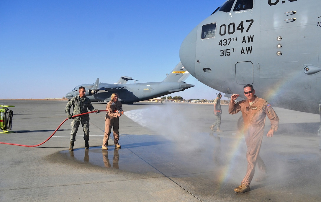 """Lt. Col. Stephen Clements, a Reservist with the 313th Airlift Squadron, Joint Base Lewis-McChord, Wash., is showered with """"praise"""" as he exits a C-17 in Southern Afghanistan.  Clements logged his 10,000th flying hour Oct. 20 while flying missions with the 405th Air Expeditionary Group in and out of Afghanistan. (U.S. Air Force photo)"""