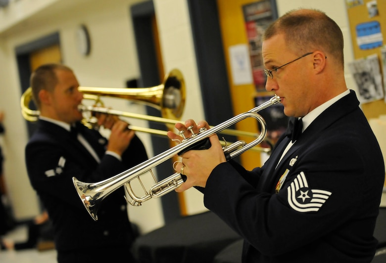 """From right, U.S. Air Force Heritage of America Band members Tech. Sgt. Mark Nixon, trumpeter, and Airman 1st Class Trent Lockhart, tromboneist, warm up prior to the start of their """"Side by Side"""" concert with the College of William and Mary Wind Ensemble at Warhill High School in Williamsburg, Va., Nov. 14, 2013. The bands played more than 11 songs during the two-hour concert that drew a crowd of more than 400 people. (U.S. Air Force photo by Staff Sgt. Wesley Farnsworth/Released)"""