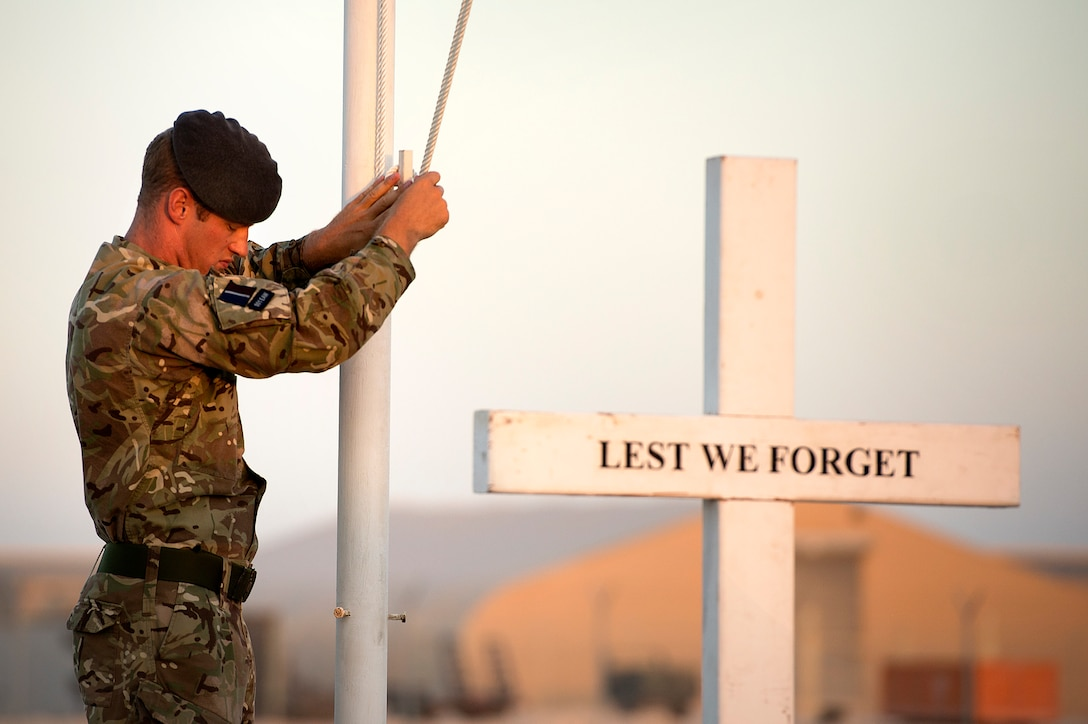 Royal Air Force Cpl. Olie Dunk pauses while lowering the English Union Flag during a sunset remembrance ceremony at the 83rd Expeditionary Air Group headquarters Nov. 9, 2013. The RAF's 83 EAG is responsible for all English units operating in Afghanistan and the Middle East. (USAF Photo by Master Sgt. Ben Bloker)