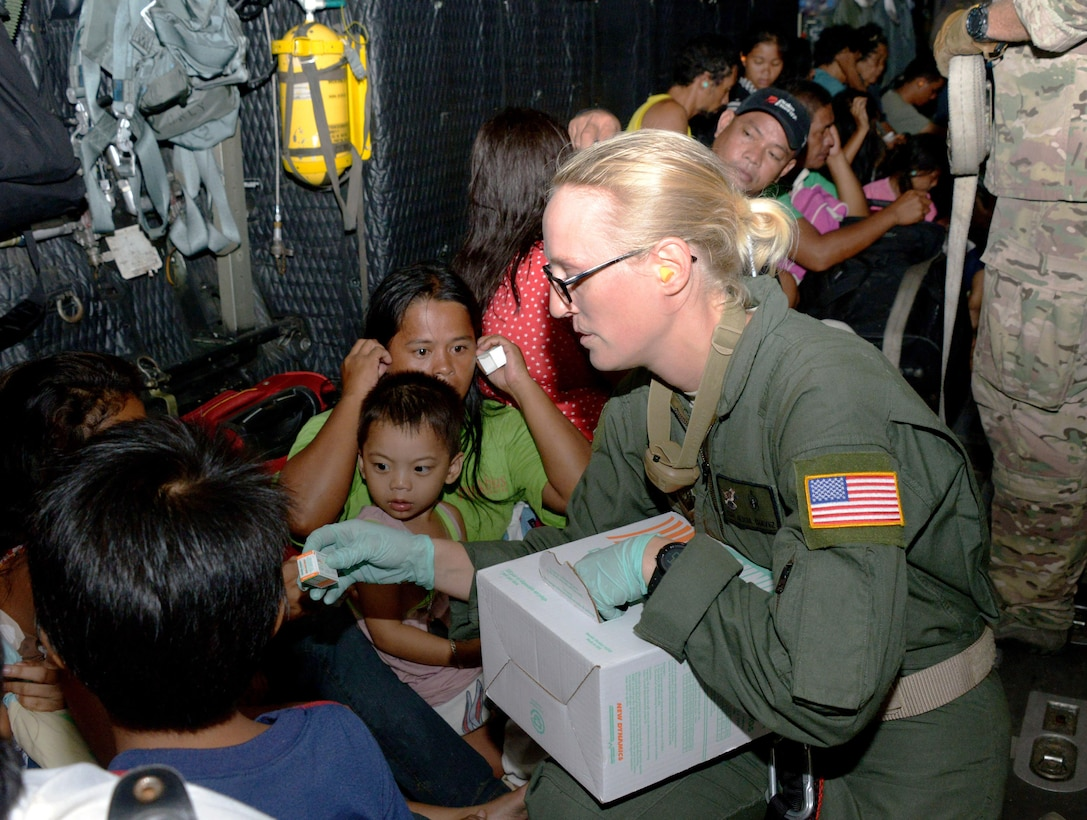 Staff Sgt. Alicia Chavez passes out ear plugs to displaced people onboard an MC-130P Combat Shadow Nov. 14, 2013, as they are transported from Tacloban Airport to Manila, Philippines. Air Force Special Operations Command Airmen are deployed in support of Operation Damayan, enabling night operations to facilitate the flow of aid. The role of U.S. military forces during any foreign humanitarian assistance event is to rapidly respond to mitigate human suffering and prevent further loss of life. Chavez is a 353rd Special Operations Support Squadron independent duty medical technician. (U.S. Air Force photo/Tech. Sgt. Kristine Dreyer)