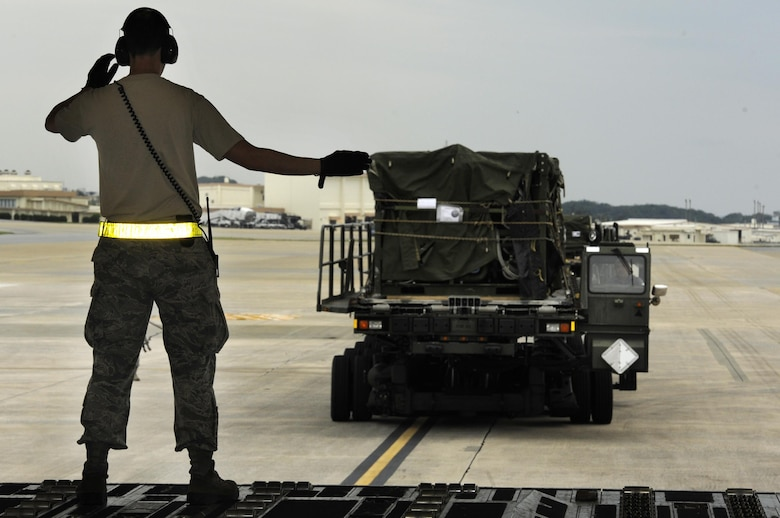 Staff Sgt. Christopher Fleury guides a cargo truck to a C- 17 Globemaster III from Joint Base Pearl Harbor-Hickam, Hawaii, on Kadena Air Base, Japan, Nov. 15, 2013. Water purifiers and military personnel are being sent to the Philippines to help the locals after the devastation caused by Super Typhoon Haiyan. Fleury is a 733rd Air Mobility Squadron air freight supervisor. (U.S. Air Force photo/Senior Airman Marcus Morris)