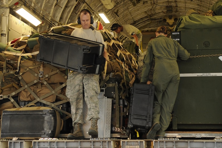 Airmen from the 733rd Air Mobility Squadron load supplies onto a C- 17 Globemaster III from Joint Base Pearl Harbor-Hickam, Hawaii, on Kadena Air Base, Japan, Nov. 15, 2013. Water purifiers and military personnel are being sent to the Philippines to help the locals after the devastation caused by Super Typhoon Haiyan. (U.S. Air Force photo/Senior Airman Marcus Morris)