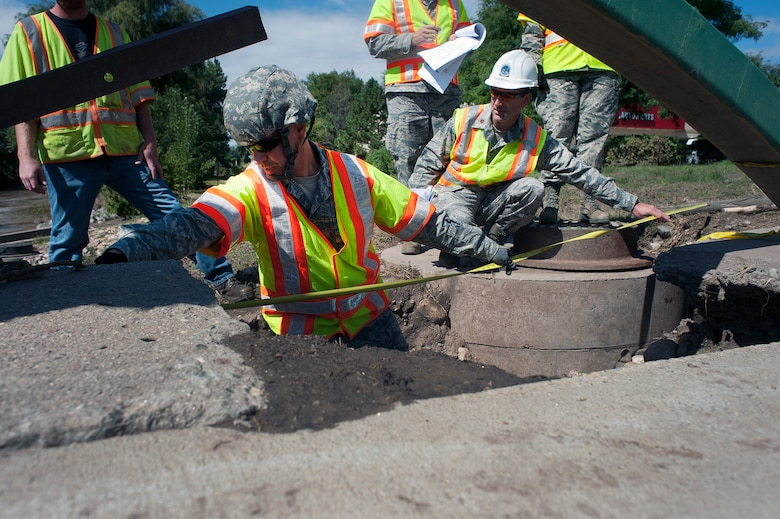 Members of the Colorado Air National Guard's 240th Civil Engineering Flight use a tape measure to measure the size of damage to a bridge affected by floodwaters in Loveland, Colo., Thursday, Sept. 19, 2013. Members of the squadron have been working with the Colorado Department of Transportation assessing the structural integrity of bridges throughout areas affected by the flooding. More than 750 guard members have been working with local, state and federal authorities in response to flooding in central Colorado as a result of heavy rains in the area.