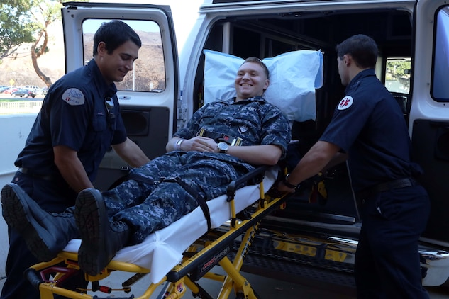 Robert Miller and Chris Anderson lift a simulated patient into an ambulance during a patient relocation drill held at Naval Hospital Camp Pendleton Nov. 15. Corpsmen posed as different types of patients to give participants a chance to see what to expect during the actual relocation on Dec. 14. Miller and Anderson are both emergency medical technicians.