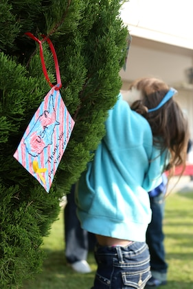 A student from Matthew C. Perry Elementary School aboard Marine Corps Air Station Iwakuni, Japan, hangs a handmade ornament on the tree located outside the school's entrance for the Veterans Day ceremony Nov. 6, 2013. Students made ornaments honoring family members that have served or are currently serving.