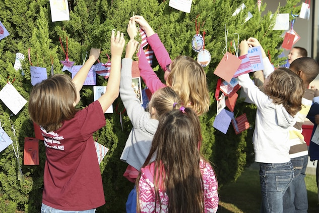 Children from Matthew C. Perry Elementary School hang ornaments on a tree located outside the school's main entrance during the Veterans Day ceremony aboard Marine Corps Air Station Iwakuni, Japan, Nov. 6, 2013. Landrum said the ornaments will stay on the tree as long as weather permits.