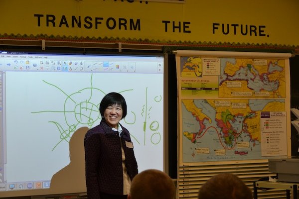 Civil Engineer Qing Xu illustrates a point by drawing a city layout and roads that come into it with students at the James Wood High School Career Fair, Nov. 13.