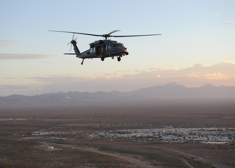 An HH-60 Pavehawk from the 55th Rescue Squadron at Davis-Monthan Air Force Base, Ariz., flies over Tucson, Nov. 13, 2013, during alternate insertion and extraction training with the pararescuemen of the 48th Rescue Squadron.  (U.S. Air Force photo by 1st Lt Sarah Ruckriegle/released)