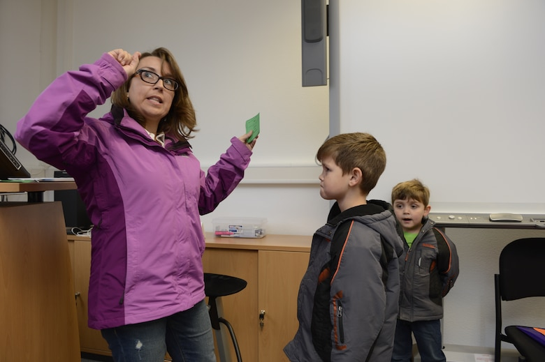 SPANGDAHLEM AIR BASE, Germany—Lee McDonough, a military spouse, left, acts out a taboo game card with her sons John, center, and Benjamin, right, to gain points during the Airman & Family Readiness Center scavenger hunt Nov. 16, 2013. For some items, families had to play games for a chance to win bonus points toward winning the scavenger hunt. (U.S. Air Force photo by Staff Sgt. Christopher Ruano/Released)
