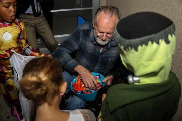 Fred Waring, station resident, passes out candy to the trick-or-treaters roaming the streets of Marine Corps Air Station Iwakuni, Japan, during the Halloween Festival Oct. 31, 2013. A total of 302 visitors came aboard station to partake in the festivities; 139 were adults.