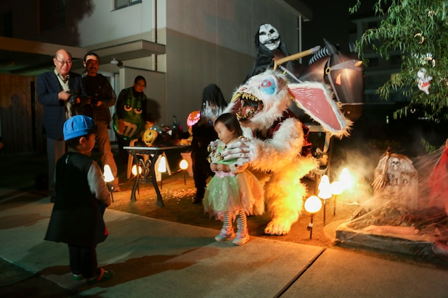 Mao Fuchikawa, 2, right, and Anji Nishimura, 3, approach a house decorated testing brave trick-or-treaters to collect candy aboard Marine Corps Air Station Iwakuni, Japan, during the Halloween Festival Oct. 31, 2013. Among the 302 visitors coming aboard station to partake in the Halloween festivities, 163 were children.