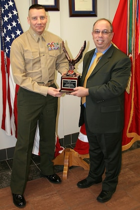 Col. Michael Manning, Marine Corps Systems Command's program manager for Infantry Weapons Systems, congratulates Salvatore Fanelli on winning the Donald Roebling Award, which honors an acquisition civilian. He worked on the acquisition, fielding and support of Mk318 Mod 0 and M855A1 ammunition to the warfighter.