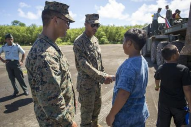 Lance Cpl. Raynaldo Olvera, from Dallas, TX., and Lance Cpl. Javan William, from the Virgin Islands, are thanked for their service by local Tinian children Nov. 11 after a Veterans Day and Marine Corps birthday ceremony at Tinian's Historic North Field during Exercise Forager Fury II. Olvera and William showed the children the heavy equipment they operate and how exactly they will restore the air field. Olvera is a heavy equipment mechanic and William is a heavy equipment operator with Marine Wing Support Squadron 171, Marine Aircraft Group 12, 1st Marine Aircraft Wing, III Marine Expeditionary Force.