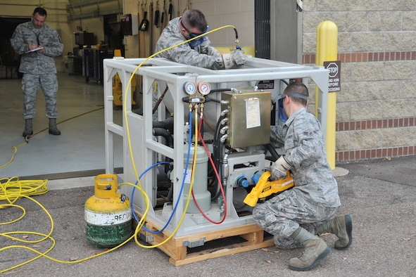 """Two Airmen from the 341st Maintenance Operations Squadron Power, Refrigeration and Electrical Section, follow a technical order to complete a task as a member of the Air Force Global Strike Command Inspector General team evaluates them in the background Nov. 14. The 341st Missile Wing was awarded an overall """"Excellent"""" rating following a weeklong Nuclear Operational Readiness Inspection Nov. 12 to 18. (U.S. Air Force photo/John Turner)"""